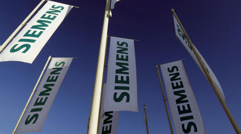 FILE - In this Jan. 23, 2013 file photo flags of German engineering conglomerate Siemens AG fly during an annual shareholder meeting in Munich, southern Germany. German industrial conglomerate Siemens AG says Friday, July 21, 2017 it's halting deliveries of power generation equipment to state-controlled companies in Russia and selling its stake in a Russian company that offers services for power plant control systems. (AP Photo/Matthias Schrader, File)